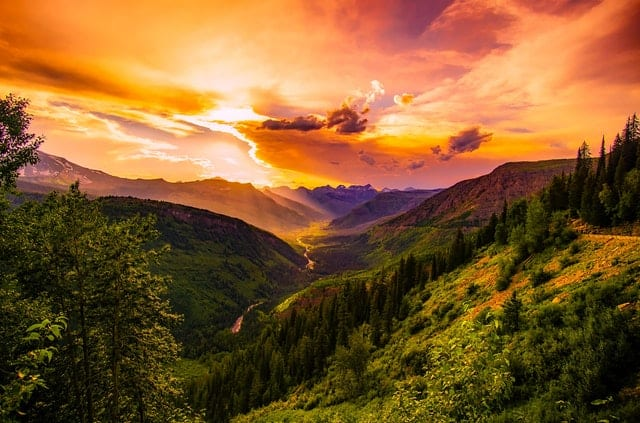 green-mountain-near-river-under-cloudy-sky-valley