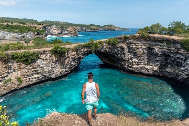 photo-of-man-standing-on-cliff-near-lagoon